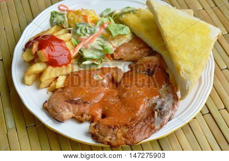grilled pork steak dressing gravy and french fried with salad on plate