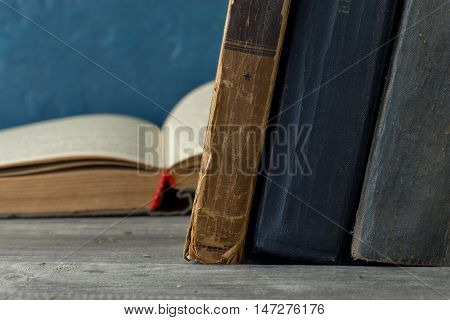 Vintage antiquarian tattered books on wooden table close up