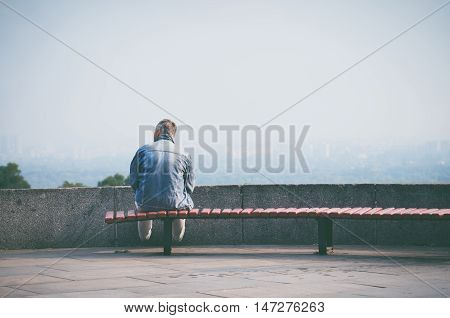 Old man sitting on a bench on the viewpoint