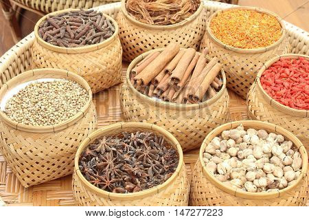 The Spices herbs in bamboo basket on background