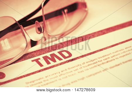 TMD - Temporomandibular Disorder - Printed Diagnosis with Blurred Text on Red Background with Pair of Spectacles. Medical Concept. 3D Rendering.