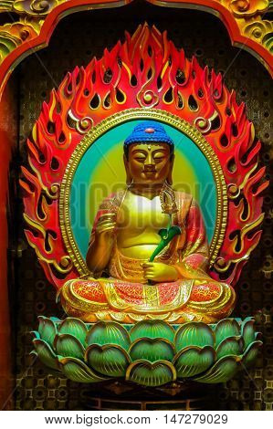 Buddha image that is carved of wood. Buddha sitting in a lotus flower and his hands is in various positions mudras