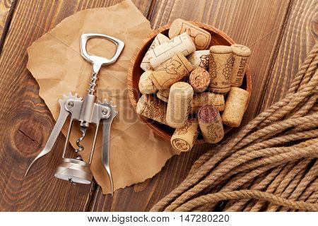 Wine corks and corkscrew over rustic wooden table background