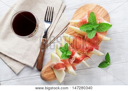 Fresh melon with prosciutto and mint. Antipasti and red wine. Top view on wooden table table