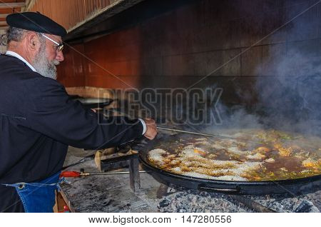 VALENCIA, SPAIN - MARCH 21, 2015: Local chef preparing a traditional Valencian paella with meat and chicken in Valencia Spain