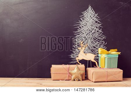 Christmas gift boxes under tree drawing on chalkboard. Alternative Christmas tree background