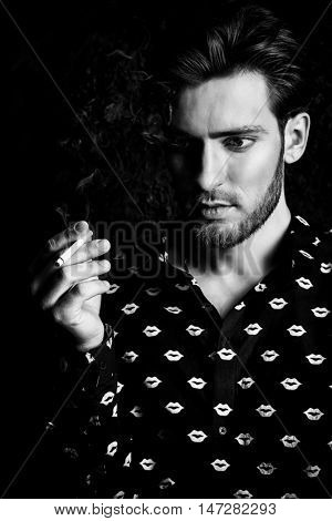 Smoking young man. Handsome young man thoughtfully and calmly smoking a cigarette. Men's beauty, fashion.