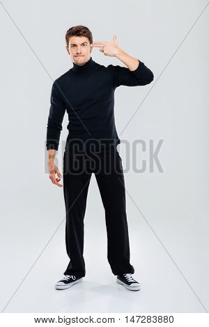 Full length of irritated young man standing with fingers to temple like a gun