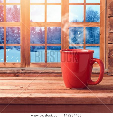 Red cup on wooden table over window with winter nature view. Winter and Christmas holiday concept. Cup mock up template for logo showcase