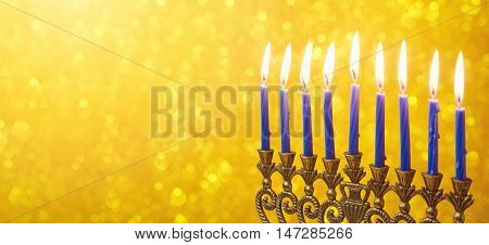 Jewish holiday Hanukkah website banner design with menorah and candles over golden bokeh
