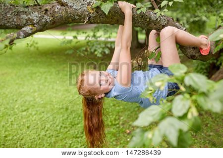 friendship, childhood, leisure and people concept - happy smiling little redhead girl hanging upside down on tree in summer park