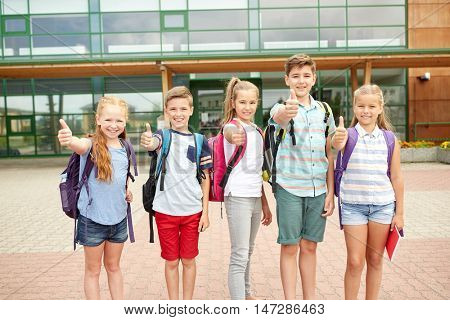 primary education, friendship, childhood, gesture and people concept - group of happy elementary school students with backpacks showing thumbs up outdoors