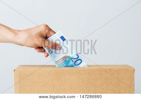 charity, finances, funding, investment and people concept - male hand putting euro money into donation box