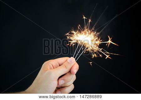 christmas, holidays, new year party and pyrotechnics concept - male hand holding sparklers or bengal light burning over black background