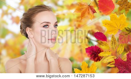 beauty, people, season and bodycare concept -beautiful young woman face and hands over autumn leaves background