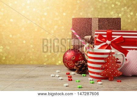 Christmas ornamnets and cup with gift boxes over gold bokeh background