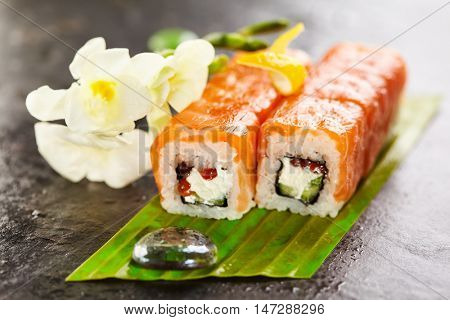 Roll with Cream Cheese, Salmon roe (ikura) and Cucumber inside. Salmon outside. Served on Banana Leaf with Flowers