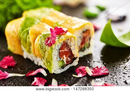Maki Sushi - Roll made of Salmon, Cream Cheese and Cucumber inside, Avocado and Cheese outside