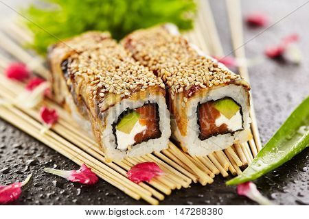 Sushi Roll with Salmon, Avocado and Cream Cheese inside. Topped with Smoked Eel (Unagi)