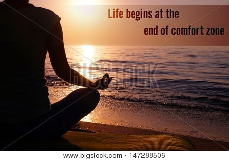 Comfort zone concept. Young healthy woman practicing yoga on the beach at sunset