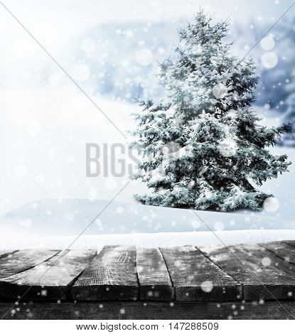 Wooden table against fir tree with snow on beautiful winter landscape