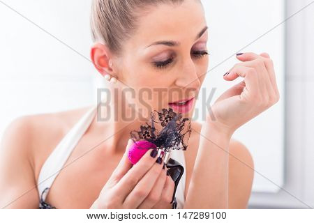 Applying of perfume on wrists in front of bathroom mirror