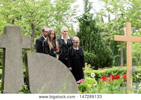 Family mourning at grave on graveyard or cemetery
