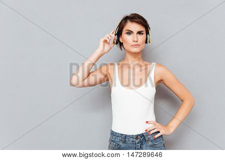 Unhappy young woman listening to music too loud and removing yellow headphones over gray background