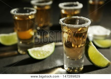 Shots of gold tequila with lime slices and salt on grey background