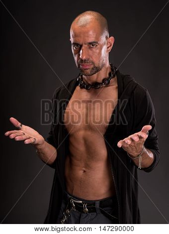 Young handsome macho man with open jacket posing on a dark background