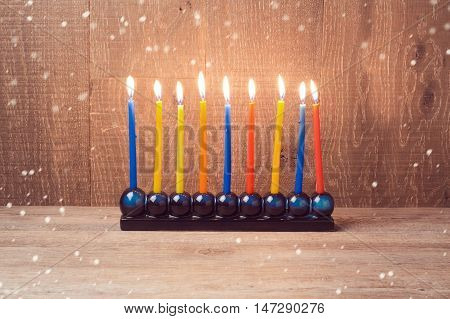 Hanukkah menorah with colorful candles over wooden background