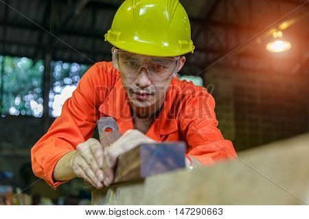 Asian young attractive man doing woodwork in carpentry