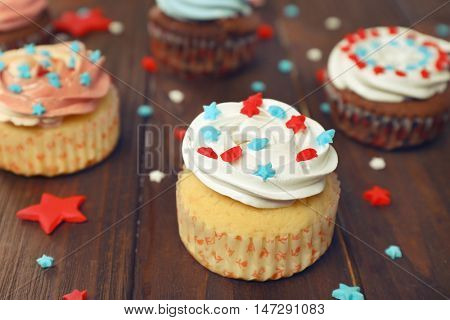 Delicious cupcakes on wooden background