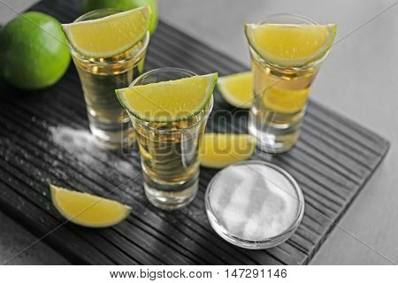 Shots of gold tequila with lime slices and salt on wooden board
