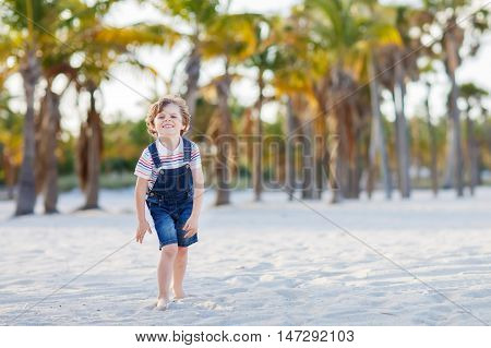 Adorable active little kid boy having fun on Miami beach, Key Biscayne. Happy cute child playing and dancing near palm trees on sunny warm day.