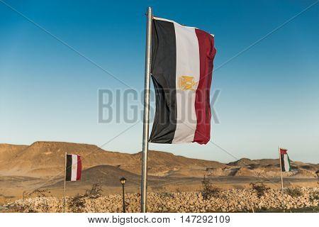 Waving Vertical Egyptian flag on metal flagpole