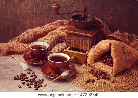 Coffee cups and vintage grinder with sackcloth over wooden background