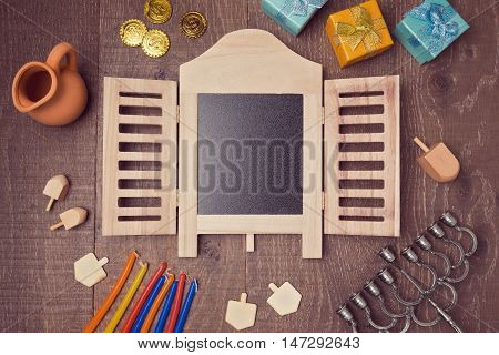 Hanukkah holiday symbols on wooden table with chalkboard. View from above