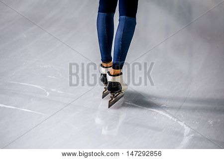 feet of a woman skater in blue tights and racing skates