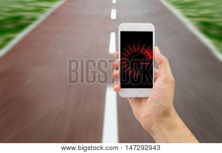 hand holding the smartphone with tachometer speed in the screen over the road in background