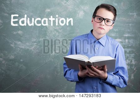 Schoolboy In Glasses With Book On The Background Of School Board With The Inscription