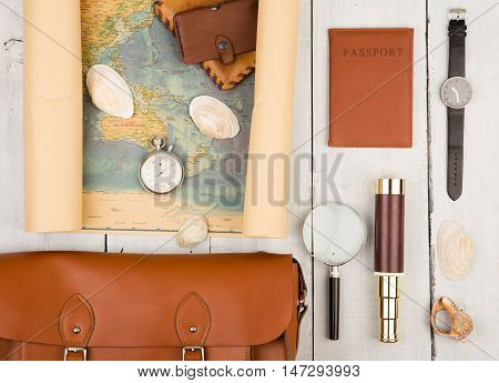 Geographic Map, Passport, Bag, Magnifying Glass, Purse, Spyglass And Stopwatch On White Wooden Table