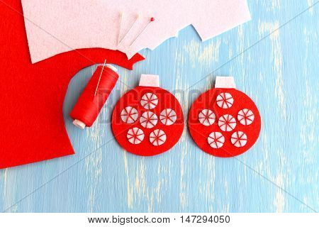 How to make a felt Christmas decoration. Tutorial. Step. Red felt balls decorated with white circles, needle, thread on a blue wooden background. Embroidery crafts. Christmas ball decor. Top view