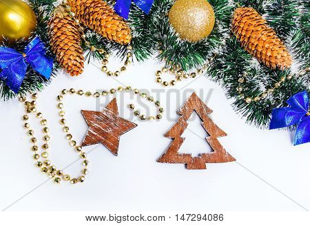 Wooden shapes of christmas tree and star, garland and tinsel, golden balls, blue ribbon bows and dry pine cones on white background. Christmass and New Year concept.