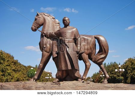 a monument to Cossack with a horse on a background of blue sky