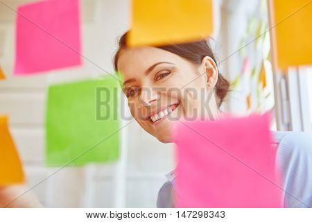 Smiling successful businesswoman gathering ideas on sticky notes