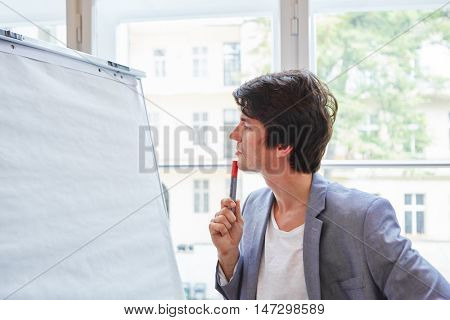 Young businessman from start-up with pen in front of Flipchart