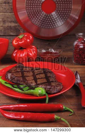 red theme lunch : fresh grilled bbq roast beef steak on red plate green chili tomato soup ketchup sauce paprika small jug glass ground pepper american peppercorn modern cutlery served on wooden table