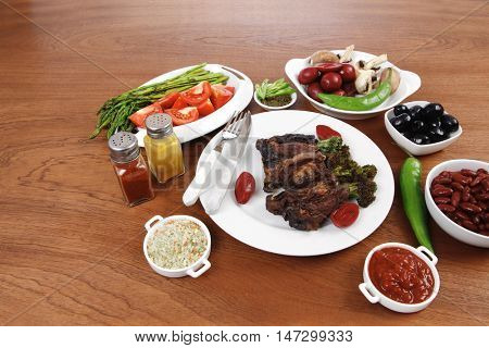 lunch of grilled meat served on big white plate with asparagus pickles tomatoes olives hot black red green pepper salt baked beans and ketchup on wooden table