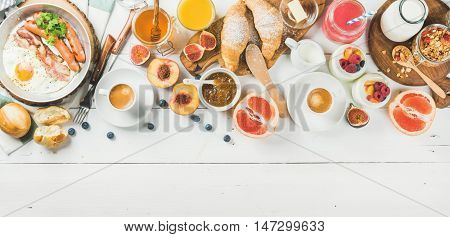 Breakfast concept food frame. Fried egg with sausages and bacon, bread, croissants, jam, fruit, smoothie, juice, yogurt, granola with milk and coffee on white wooden background. Top view, copy space